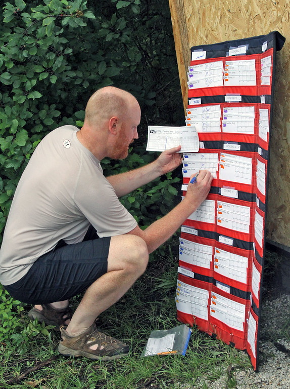 . Disc Golf Tournament Dir., Bill Bertera of Shirley, tallies the players scores after the 2nd round in Devens. SUN/David H. Brow