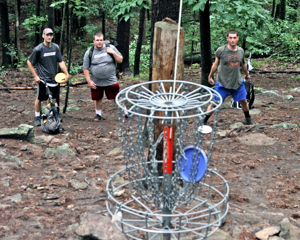 . Tyler Blanchet,24,on far right, watches as his disc lands in the basket as his team-mates. Paul Adorno,36 and Chris Spears,26 all from Connecticut look on. SUN/David H. Brow