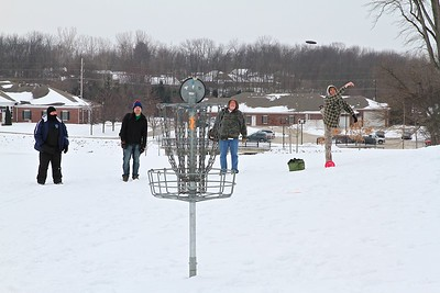 L-R John Strifler, Jeremy Sumpter, and Sam Taylor watch as Matt Berry putts on Hole One of the Hendricks County Disc Golf 2015 Ice Bowl Tournament.