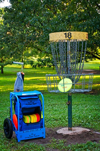 My disc golf cart, bag and discs at hole 18 of the Prairie Center Disc Golf Course