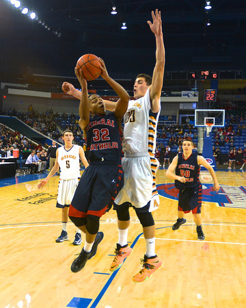 RYAN HUTTON/ Staff photo.<br /> Central Catholic's Alexander Santos (32) puts up a shot as Andover's Nicholas Boes (33) tries to block during the first half of Saturday night's game at the Tsongas Center in Lowell.