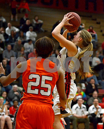 -Messenger photo by Britt Kudal<br /> Madi Bennett of Fort Dodge shoots over Ames' Deja McAtte on Friday inside Dodger gym