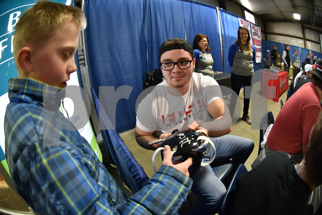 -Messenger photo by Britt Kudla<br /> Fort Dodge Cael Pavik has Tristion Licht signs his wrestling head gear during the Home and Lifestyle Show on Saturday