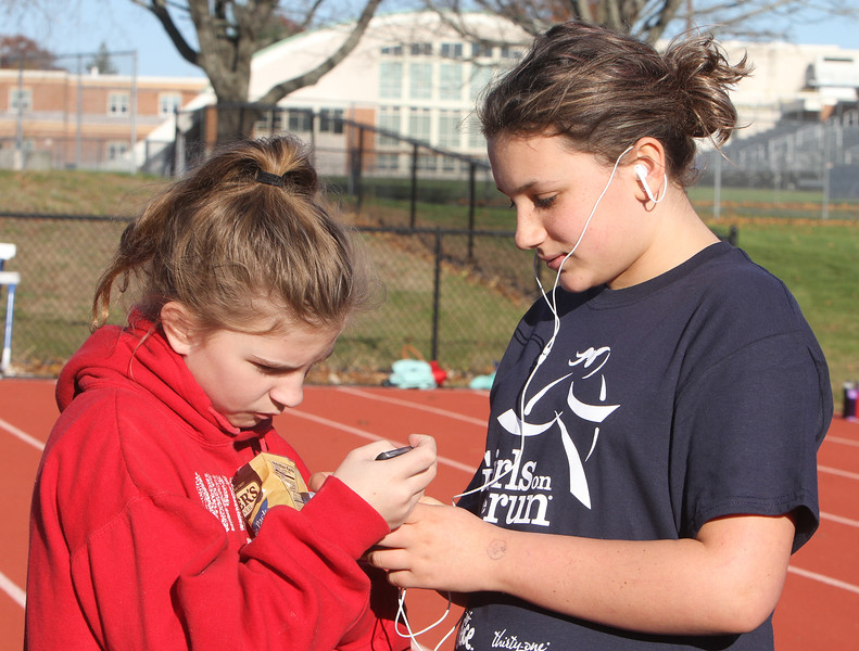 Girls on the Run in Dracut hold a practice 5K at Dracut High, to get ready for an upcoming regional 5K against other Girls on the Run groups. Elizabeth Matte, 11, left, and Hannah Volpe, 13, before the race. (SUN/Julia Malakie)
