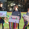 Girls on the Run in Dracut hold a practice 5K at Dracut High, to get ready for an upcoming regional 5K against other Girls on the Run groups. Holding signs with streamers to count laps, from left, sophomore Derick Ocasio, senior Kyle Supernor, and 8th grader Nick Grier. (SUN/Julia Malakie)