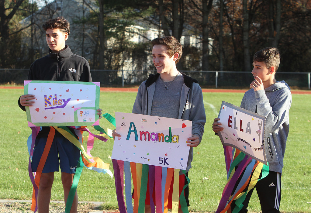 . Girls on the Run in Dracut hold a practice 5K at Dracut High, to get ready for an upcoming regional 5K against other Girls on the Run groups. Holding signs with streamers to count laps, from left, sophomore Derick Ocasio, senior Kyle Supernor, and 8th grader Nick Grier. (SUN/Julia Malakie)