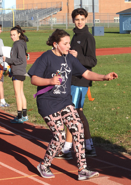 Girls on the Run in Dracut hold a practice 5K at Dracut High, to get ready for an upcoming regional 5K against other Girls on the Run groups. Hannah Volpe, 13, of Dracut, daughter of coach Allison Volpe, reaches out for a streamer/lap counter. Looking on is sophomore track team member Derick Ocasio. (SUN/Julia Malakie)