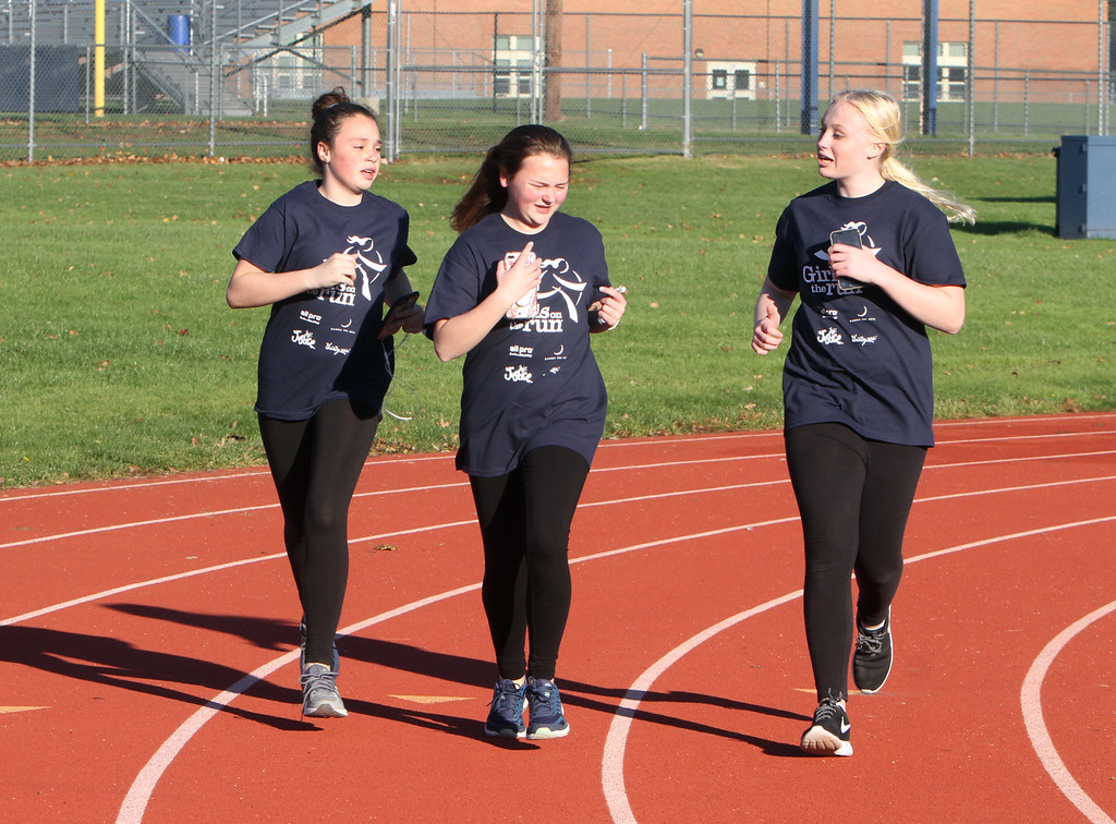 . Girls on the Run in Dracut hold a practice 5K at Dracut High, to get ready for an upcoming regional 5K against other Girls on the Run groups. From left, Ella Keefe, 11, Keara Rowe, 13, and Trinity Caruso, 13, run together. (SUN/Julia Malakie)