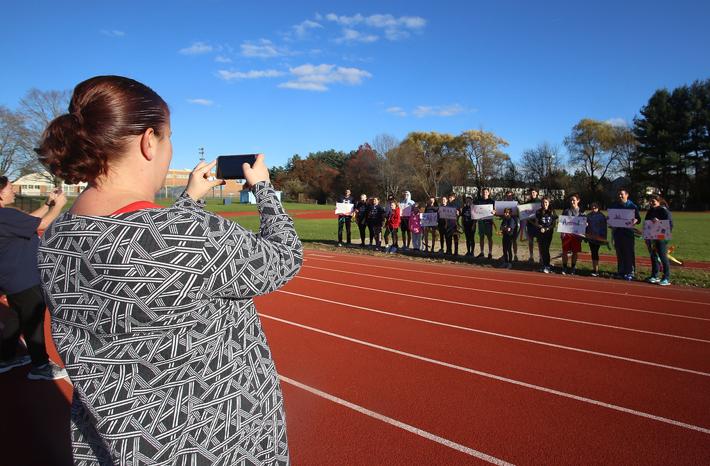 . Girls on the Run in Dracut hold a practice 5K at Dracut High, to get ready for an upcoming regional 5K against other Girls on the Run groups. Coach Christine Lord takes a picture of the team and their sign holders, many from the Dracut High track team. (SUN/Julia Malakie)