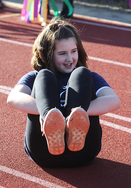 "Girls on the Run in Dracut including Ally Buote, do warmup exercises including ""the boat"" before a practice 5K at Dracut High, to get ready for an upcoming regional 5K against other Girls on the Run groups. (SUN/Julia Malakie)"