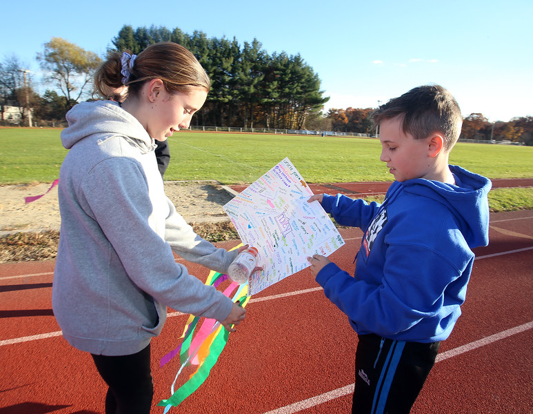 Girls on the Run in Dracut hold a practice 5K at Dracut High, to get ready for an upcoming regional 5K against other Girls on the Run groups. 8th grader Hailey Talbot pulls a lap counter from her sign, held by Brad Volpe, 11, son of coach Allison Volpe. (SUN/Julia Malakie)