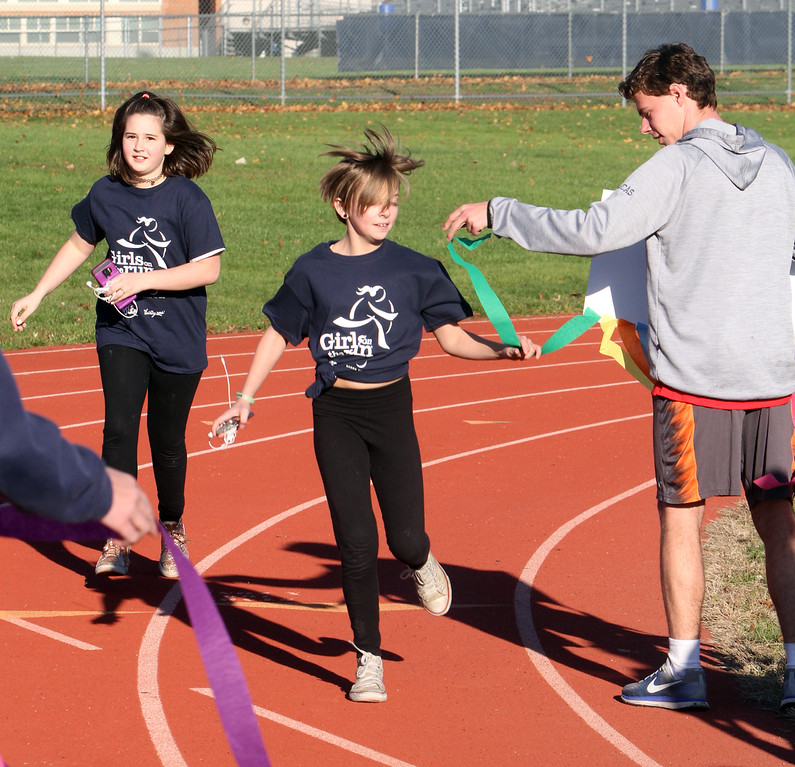 . Girls on the Run in Dracut hold a practice 5K at Dracut High, to get ready for an upcoming regional 5K against other Girls on the Run groups. Alexis Landry, 11, of Dracut, center, reaches out for a streamer/lap counter, from her sign-holder, Dracut High sophomore and track team member Lucas St. Louis. At left is Ally Buote. (SUN/Julia Malakie)