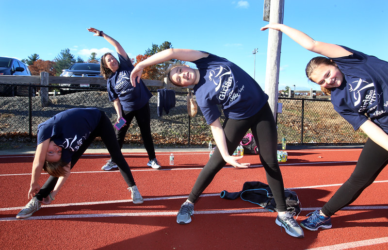 """Girls on the Run in Dracut do warmup exercises including the """"banana pose"""" before a practice 5K at Dracut High, to get ready for an upcoming regional 5K against other Girls on the Run groups. From left, Alexis Landry, 11, coach Allison Volpe, Ella Keefe, 11, and Keara Rowe, 13, all of Dracut. (SUN/Julia Malakie)"""