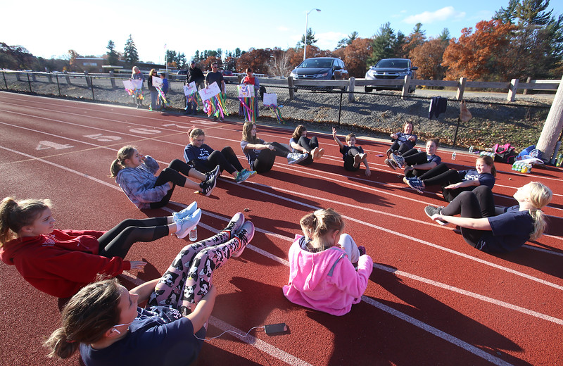 """Girls on the Run in Dracut do warmup exercises including """"the boat"""" before a practice 5K at Dracut High, to get ready for an upcoming regional 5K against other Girls on the Run groups. (SUN/Julia Malakie)"""
