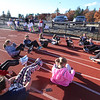 "Girls on the Run in Dracut do warmup exercises including ""the boat"" before a practice 5K at Dracut High, to get ready for an upcoming regional 5K against other Girls on the Run groups. (SUN/Julia Malakie)"