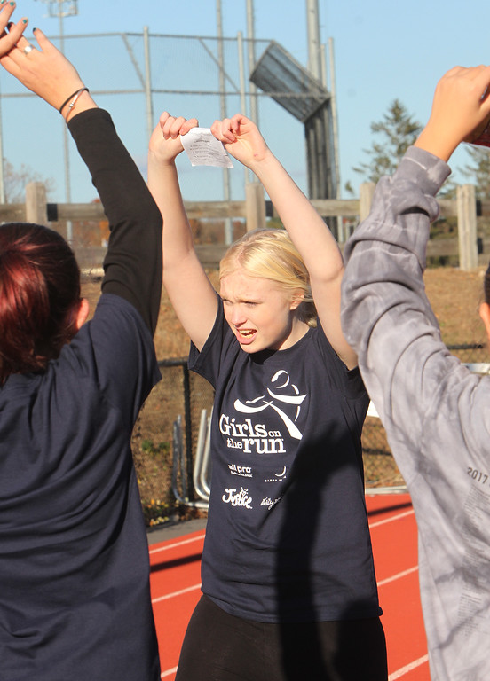 . Girls on the Run in Dracut hold a practice 5K at Dracut High, to get ready for an upcoming regional 5K against other Girls on the Run groups. Trinity Caruso, 13, of Dracut, center, helps lead warmup exercises. (SUN/Julia Malakie)
