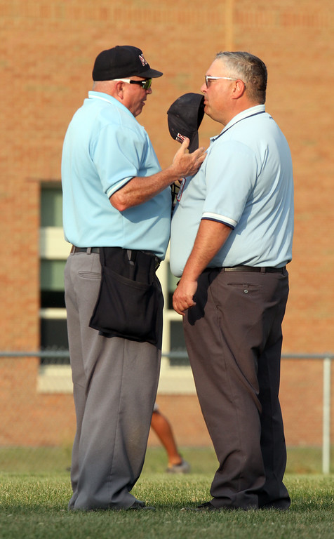 . Dracut vs Lowell Northeast Summer Baseball. Home plate umpire Dennis Hansbury of Tyngsboro, left, and infield umpire Jim Ricoy of Lowell, confer after Hansbury called a ball after a Dracut batter was hit on the elbow, ruling that the batter turned into the pitch intentionally. (SUN/Julia Malakie)