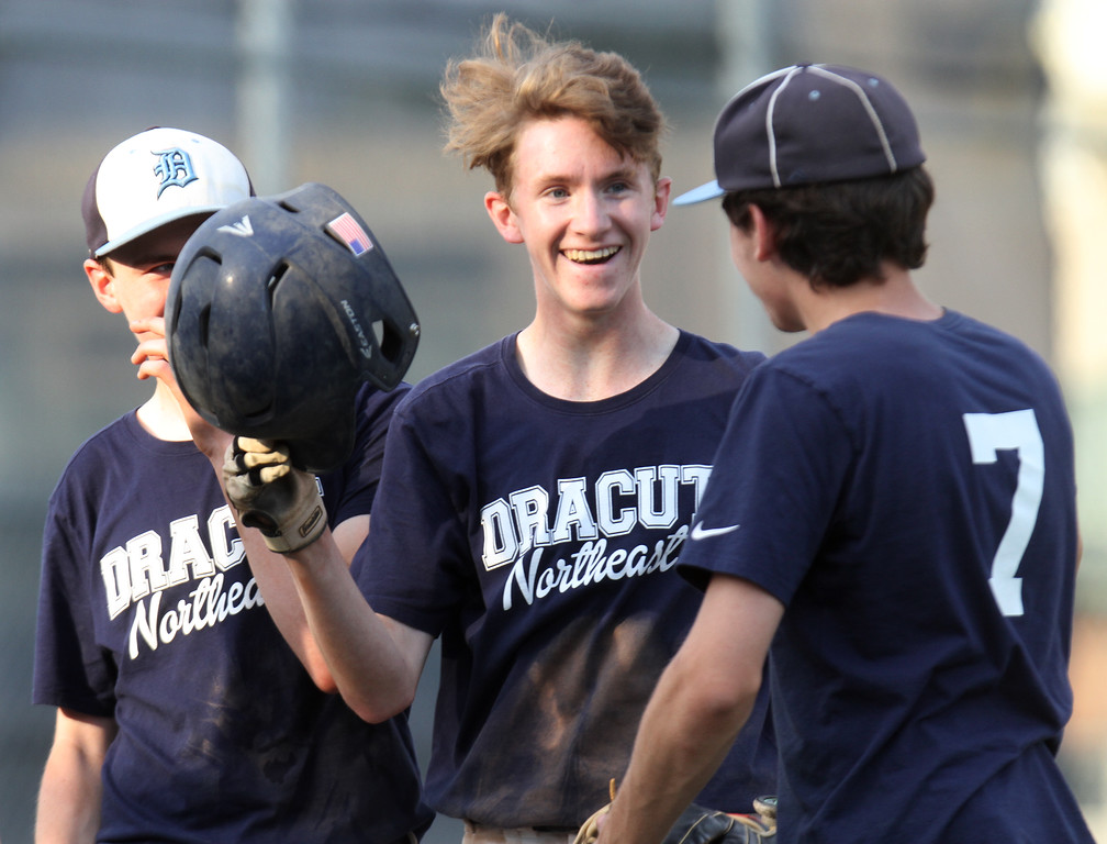 . Dracut vs Lowell Northeast Summer Baseball. Dracut\'s Sean McMeniman (10), center, scores in the bottom of the second after his triple, and a double by Mike Moore. At right is Pat O\'Toole (7). (SUN/Julia Malakie)