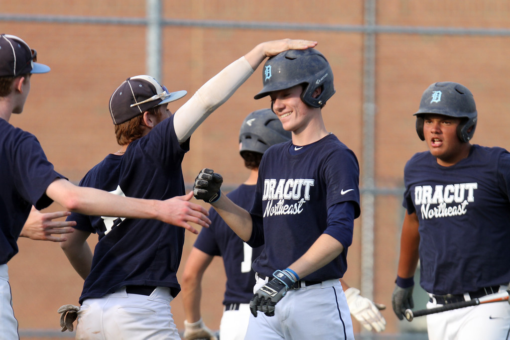 . Dracut vs Lowell Northeast Summer Baseball. Dracut\'s Jack Leahy (3), center, getting a pat on the head from Kyle Cox (8), and Mike Moore (18), right, score in the bottom of the second inning. (SUN/Julia Malakie)