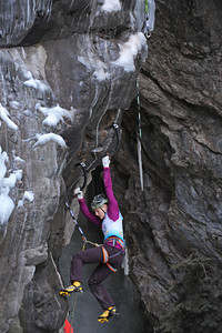 """Emily Harrington of Boulder, Colorado makes her way up the route.  She placed first among the women competitors. The 17th annual Ouray Ice festival hosted 18 elite climbers from all over the nation, Canada and France.  Three women and 15 men competed for a first place purse of $2000 for each the men's and the women's finishers.  The centerpiece for the mixed climbing event was a unique narrow manmade loaf of ice that crossed from one side of the gorge to the other while dangling 50 feet off the canyon floor. The overhanging loaf of ice, which the creators of the route called """"Povitica"""" proved to be the crux or the hardest part of the climb.  Povitica is Slovenian for sweet nut loaf.  Climbers competed against one another but also against the clock.  They had only 15 minutes to finish the route.  Only two climbers successfully completed the M10 rated route. Helen H. Richardson, The Denver Post"""