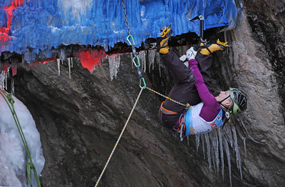"""Emily Harrington of Boulder, Colorado makes her way over the manmade portion of the climb where climbers had to cross from one side of the canyon to the other.  She placed first among the women competitors. The 17th annual Ouray Ice festival hosted 18 elite climbers from all over the nation, Canada and France.  Three women and 15 men competed for a first place purse of $2000 for each the men's and the women's finishers.  The centerpiece for the mixed climbing event was a unique narrow manmade loaf of ice that crossed from one side of the gorge to the other while dangling 50 feet off the canyon floor. The overhanging loaf of ice, which the creators of the route called """"Povitica"""" proved to be the crux or the hardest part of the climb.  Povitica is Slovenian for sweet nut loaf.  Climbers competed against one another but also against the clock.  They had only 15 minutes to finish the route.  Only two climbers successfully completed the M10 rated route. Helen H. Richardson, The Denver Post"""