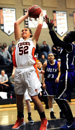 Erie High School's Taryn Lee (52) pulls down a rebound as Denver South's Biag Mayek (12) defends during their game at Erie High School on Wednesday February 22, 2012. <br /> Photo by Paul Aiken / The Camera / Boulder