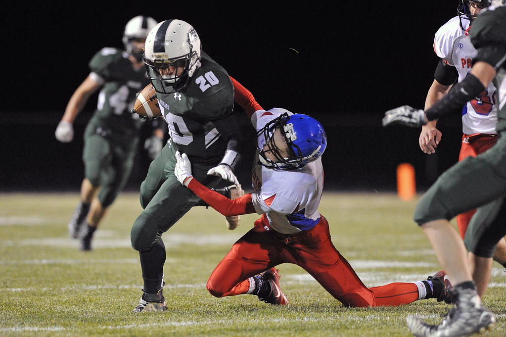 Running back Elias Dillon-Bennett (20) tries to break free from a tackle on Friday, Oct. 13 at Tongue River High School. Mike Pruden | The Sheridan Press