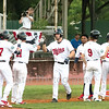 Star Photo/Larry N. Souders<br /> The Twins J.J. Robinson (35) is greeted by his teammates after blasting a three run homer on a fly ball to right center field. The homer gave the Twins a 4-1 lead.