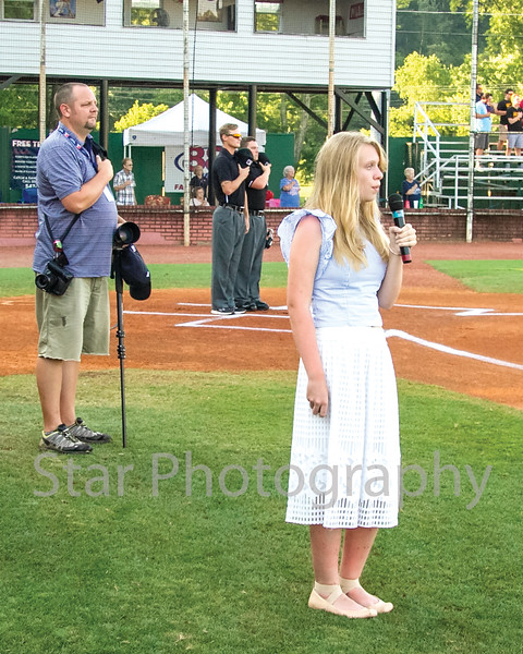 Star Photo/Larry N. Souders<br /> With Robert Kell and the games umpires looking on, Elizabethton native and Providence Academy raising seventh grader Emma Grubbs (R) preforms the National Anthem prior to Wednesday nights Twins game against the Pirates of Bristol.