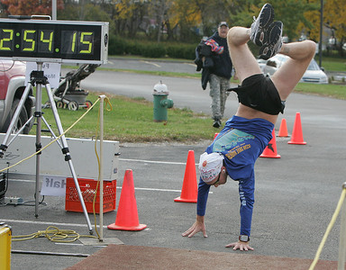 "1NOV09  Mark Ott of Jackson, Michigan,'marks' his personal tradition of doing a handstand at the finish line.  ""It's been a traditon I started 20 marathons ago in January of 2008,"" he said.  Elyria Inland Trail Marathon was held at Murray Ridge School. His time was slightly longer than that indicated, since the pad in the foreground records the finish time.   photo bY Chuck Humel"