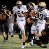 Holy Family High School junior Connor Clay is tackled by Erie High School senior Levi Hammett, left, and junior Justin Vang on Friday, Sept. 10, during a football game at Erie High School. Erie beat Holy Family 21-17.<br /> Jeremy Papasso/ The Camera