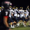 CARL RUSSO/Staff photo. Andover defeated North Andover 33-32 in overtime football action Friday night. Andover's head coach, E. J. Perry  celebrates with his players as a North Andover player walks off the field  after Andover made the extra point to win the game in overtime. 9/6/2013.