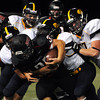 CARL RUSSO/Staff photo. Andover defeated North Andover 33-32 in overtime football action Friday night. Andover defenders surround North Andover captain, Tom Stabile for the tackle. 9/6/2013.
