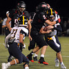 CARL RUSSO/Staff photo. Andover defeated North Andover 33-32 in overtime football action Friday night. North Andover's Tyler Salois, 9 tackles Andover's quarterback, Oliver Eberth. 9/6/2013.