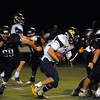 CARL RUSSO/Staff photo. Andover defeated North Andover 33-32 in overtime football action Friday night. Andover's Will Eikenberry picks up yardage as North Andover's Yanni Falaras, left and captain Collin Couillard, right move in to make the tackle.  9/6/2013.