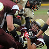 CARL RUSSO/Staff photo. Whittier Tech.'s Corey Gauthier ends up on the bottom of the pile while helping to tackle Northeast Tech.'s Kevin Rosado as he attempts to leap over Gauthier in football action.  Whittier was defeated by Northeast 18-14 in Saturday game action. 10/5/2013.