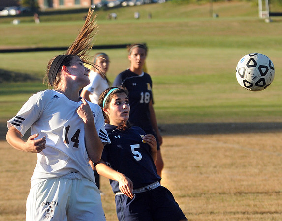 CARL RUSSO/Staff photo. Haverhill's captain, Kelleigh Cokely (14) uses her head to direct the ball away from Andover captain, Lily Puccia in Tuesday afternoon soccer action. Haverhill defeated Andover 3-1. 10/1/2013.