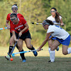 MARY SCHWALM/Staff photo  North Andover's Shannon Cronin, left, vies for the ball against Methuen's Nina Correia during their field hockey game in Methuen.  9/11/13