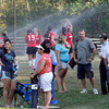 MARY SCHWALM/Staff photo  Parents and fans move as North Andover junior varsity players cool off in the sprinklers before the start of the varsity field hockey game against Methuen in Methuen. 9/11/13