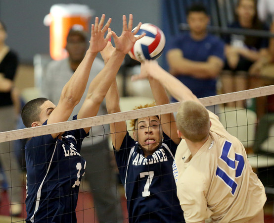 Lawrence defenders Christian Taveras (13) and Joel Carmona (7) leaps to try and block a spike attempt from Acton-Boxboro's Matthew Locklin during their Division 1 North Volleyball final game in Lawrence.  Acton-Boxboro won in five sets.