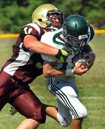 CARL RUSSO/Staff photo. Whittier Tech. was defeated by Austin Prep 22 to 14 in Saturday morning football action. Whittier's Sidney Taylor is forced to tackle Austin Prep's Jonathan Saurman of Pelham after Saurman intercepted the pass intended for Taylor. 9/7/2013.