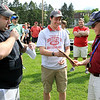 Greg Rodriquez, left, Class of 2003, reads about the plaque being presented to longtime Fitchburg High School track coach Chris Woods, right, during a ceremony before the start of Saturday's Mid-Wach A championship meet at Crocker Field. Woods will retire after this season, ending a career that spanned more than three decades at the high school. SENTINEL & ENTERPRISE / SCOTT LAPRADE