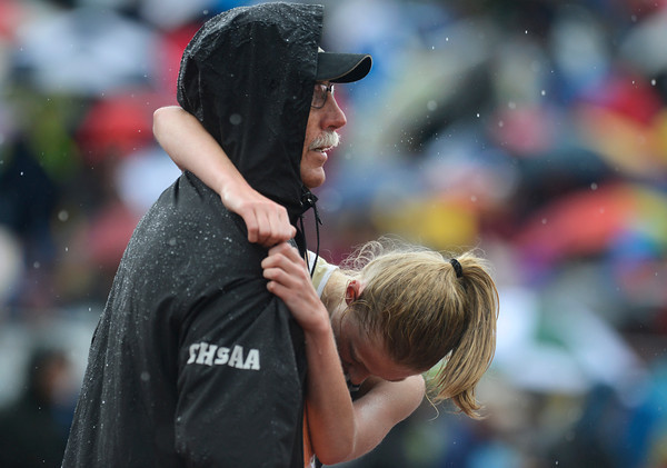 Nederland's Kelley Robinson, right, holds onto an official after the end of the 2A girls 1600 meter run during the last day of the 2012 Colorado High School State Track and Field Championships at Jefferson County Stadium on Saturday, May 19, 2012. Robinson finished second in the race.<br /> (Greg Lindstrom/Times-Call)