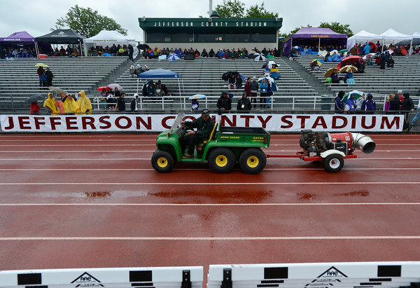 Officials try to dry the track after a rain shower during the last day of the 2012 Colorado High School State Track and Field Championships at Jefferson County Stadium on Saturday, May 19, 2012.<br /> <br /> (Greg Lindstrom/Times-Call)