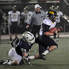 CARL RUSSO/Staff photo. St. John's Prep. defeated Andover 21-0 in Division One football playoff action Tuesday night. Andover's captain and quarterback, C. J. Scarpa tries to break away from St. John's Christopher Newton holding onto the ball with is bloody arm. 11/27/2012.
