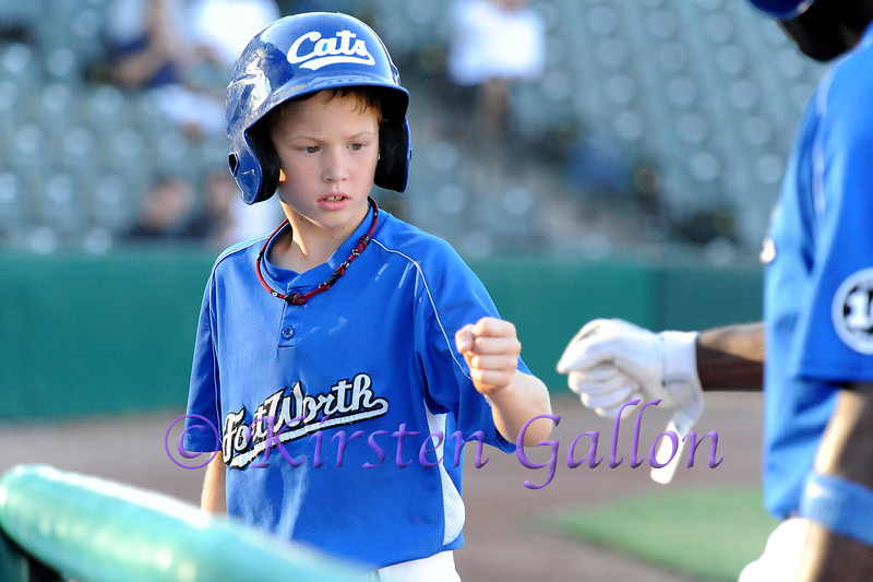 One of the bat boys gets a fist bump from a Cats player.