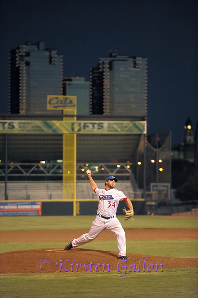 Kane pitching with the downtown Fort Worth skyline in the background.