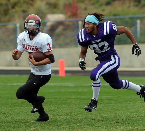"Fairview quarterback, Michael McVenes, tries to get away from Devon Beck of Arvada West, who lost his helmet on the play.<br /> For more photos of the game, go to  <a href=""http://www.dailycamera.com"">http://www.dailycamera.com</a>.<br /> Cliff Grassmick / October 9, 2010"