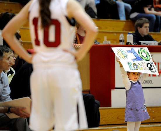 Lila Malia, 4, of Boulder, holds a sign supporting her Fairview High School cousin Meghan Higgins , at left, during a basketball game against Loveland High School on Thursday, Jan. 20, at Fairview High School. Fairview defeated Loveland 61-39. <br /> Jeremy Papasso/ Camera