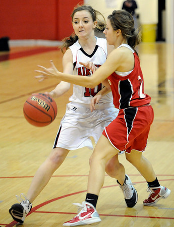 Fairview High School junior Meghan Higgins passes the ball under the arms of Loveland sophomore Michelle Petrie during a basketball game against Loveland High School on Thursday, Jan. 20, at Fairview High School. Fairview defeated Loveland 61-39. <br /> Jeremy Papasso/ Camera